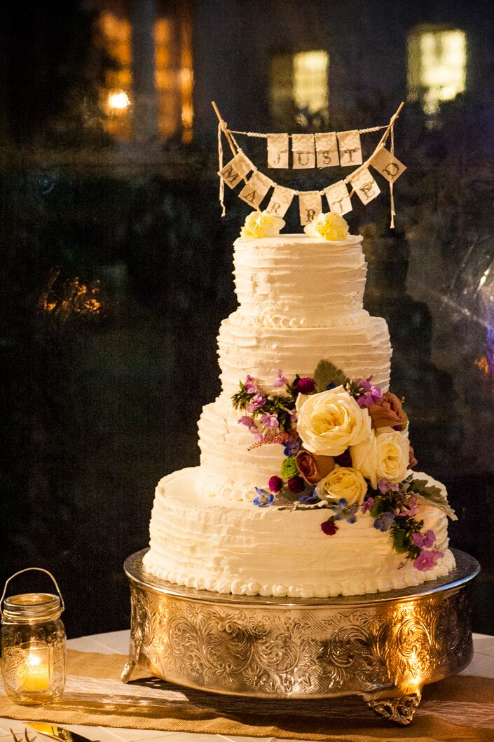 In addition to providing dinner, Jamie Hollander Catering also created an amazing white wedding cake for the reception. The raspberry and sea salt caramel cake was covered in vanilla icing and decorated with cascading roses and wildflowers.