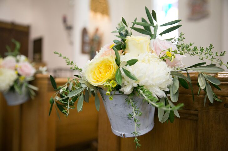 Katherine and John had Visual Impact Design line the aisles of St. Helena Catholic Church with small metal pails filled with blush, ivory and lemon yellow flowers such as garden roses and dahlias.