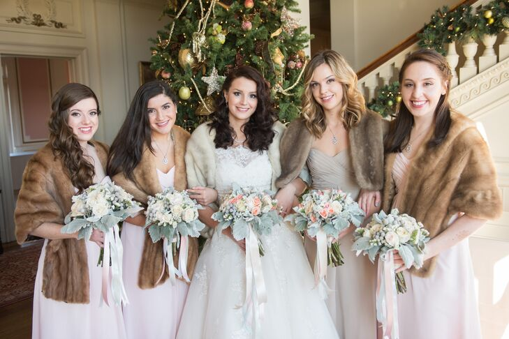 A Christmas tree at the Cairnwood Estate was decorated to fit the color scheme of the wedding. Rather than be bogged down by dark, seasonal colors, the bridal party was outfitted in light ensembles—pale pink for the bridesmaids, a light latte for the maid of honor—topped with fur shawls.