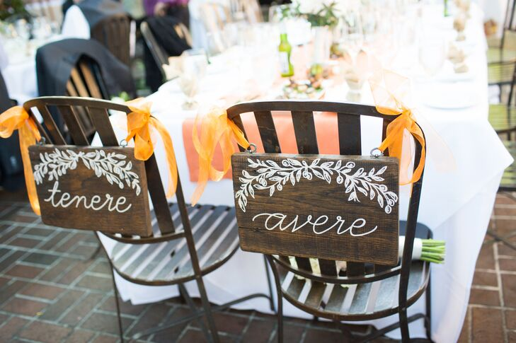 """The artist the couple commissioned to create their table numbers, seating charts and menus also crafted signs for the backs of Katherine and John's dinner chairs. Instead of traditional """"bride"""" and """"groom"""" or """"Mr."""" and """"Mrs."""" signs, the couple marked their seats with the words """"avere"""" and """"tenere,"""" which mean """"to have"""" and """"to hold"""" in Italian."""