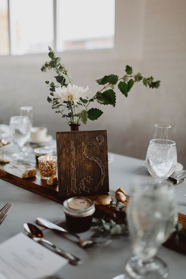 The table numbers, a collaborative effort between Shannon and Sparkle Motion Decor, perfectly captured the wedding's woodland vibe. Shannon cut and stained blocks of wood to serve as the numbers' base, then handed them off to her design team, who decorated them with gold string-art numbers that resembled vines.