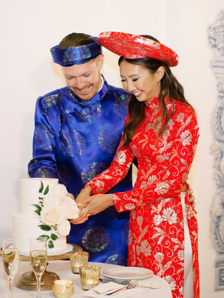 Couple cutting the cake while wearing traditional Vietnamese attire