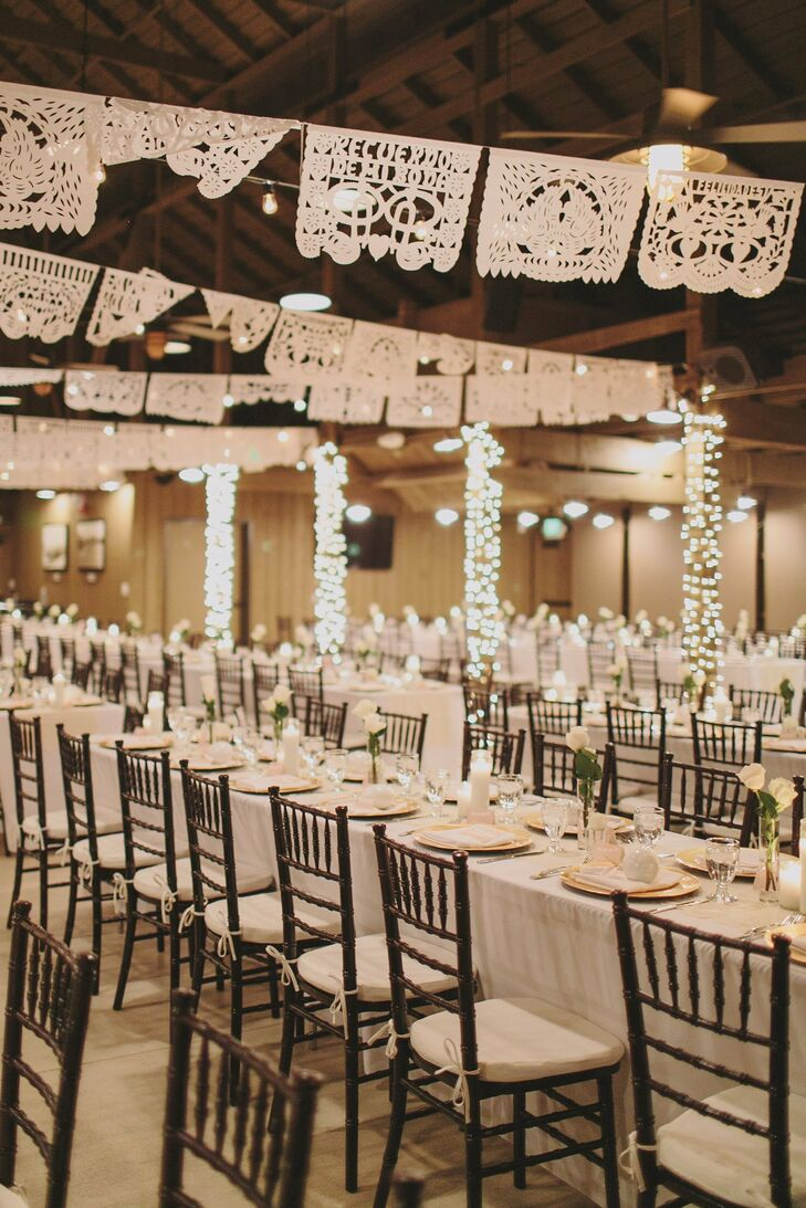 To honor their Mexican heritage in a subtle and elegant way, the couple hung a banner of white, laser-cut papel picado above the dining tables in the reception space.