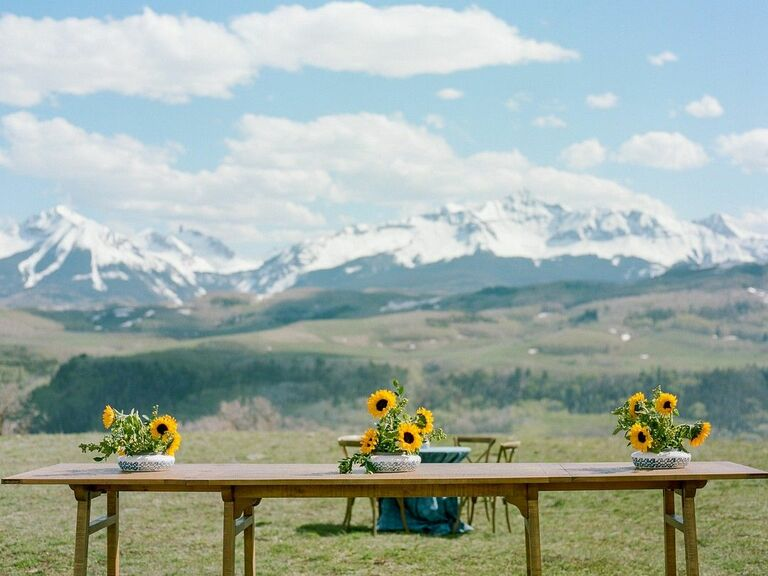 Table with sunflower centerpieces overlooking mountains