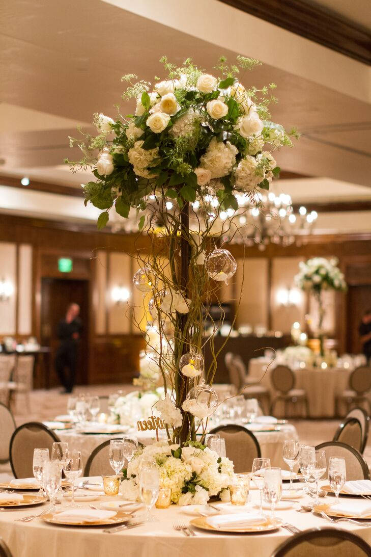 Emily and Chris used a mix of tall and short centerpieces to maximize the ballroom's vertical space. For the tall centerpieces, rounded arrangements of white hydrangea, garden roses and hanging tea lights were set atop pillar stands covered with winding curly willow.