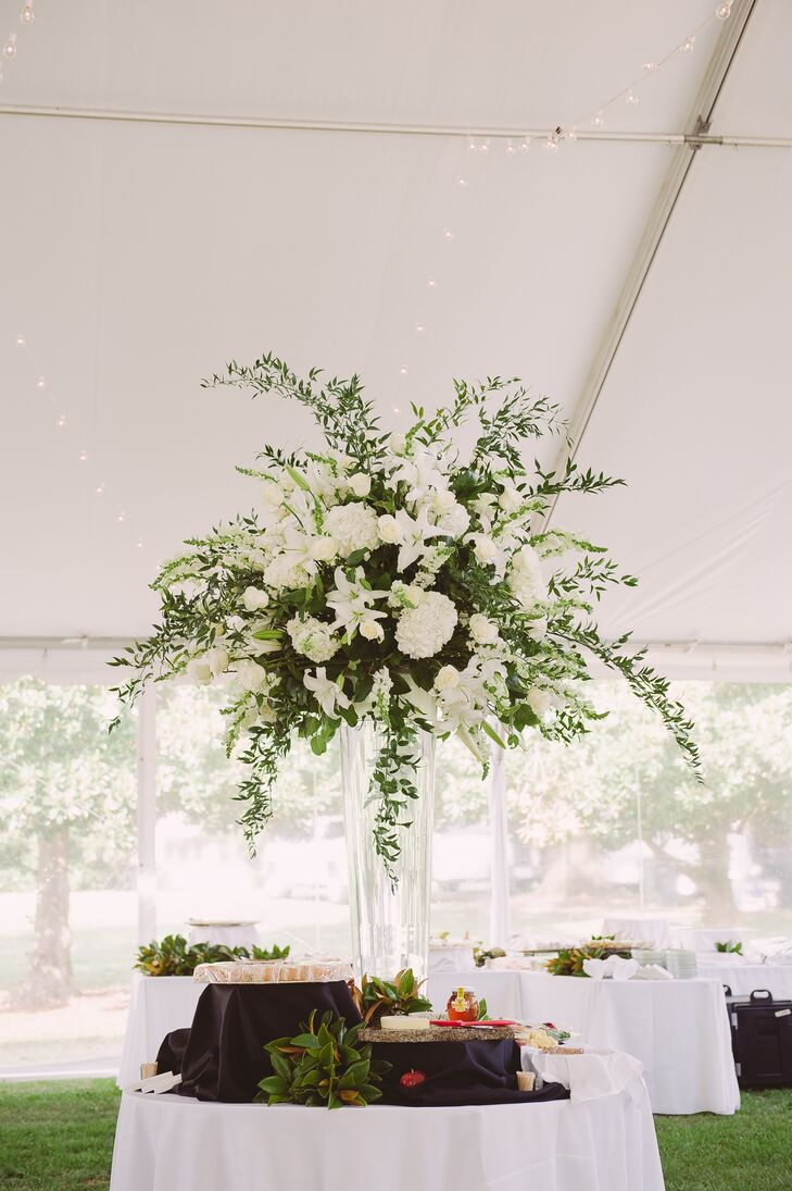 The reception tables were decorated with tower floral arrangements, including lilies, hydrangeas, roses and leafy branches. Claire and Adam loved how the floral arrangements added dimension to the tented reception.