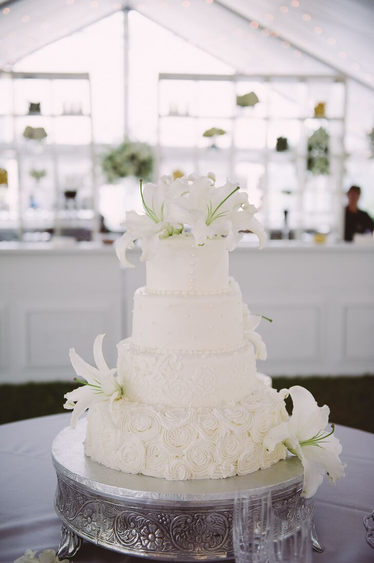 Claire and Adam enjoyed a four-tier white buttercream wedding cake for dessert. The bottom tier was decorated with buttercream rosettes to match Claire's wedding dress, and the other layers featured roses or Swiss dots. It was topped with white lilies to match Claire's bouquet.
