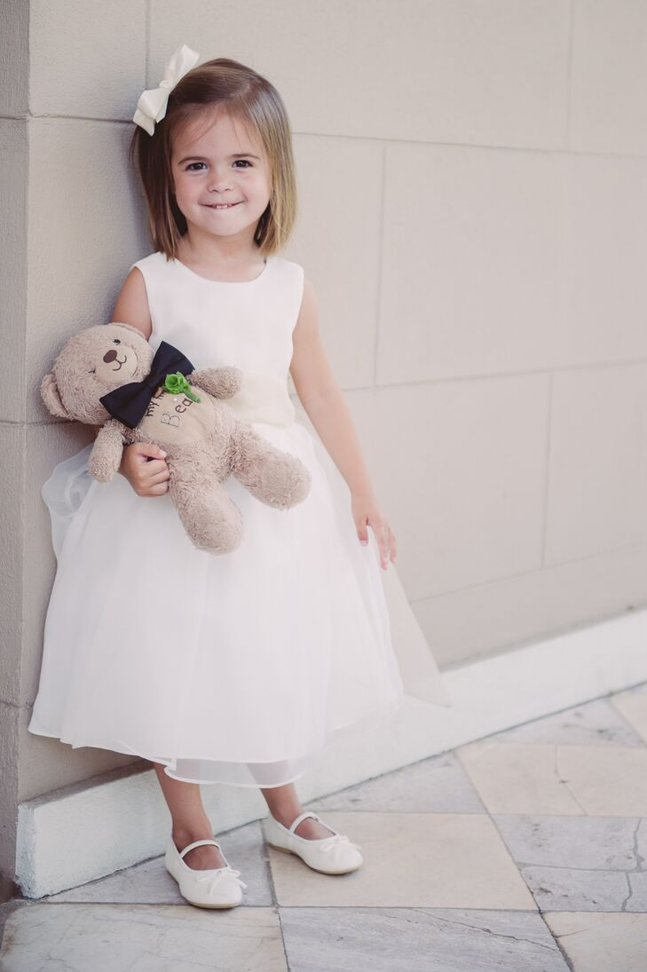 The flower girl wore a white dress with a tulle tutu. She completed her look with a white bow in her hair and white ballet shoes.