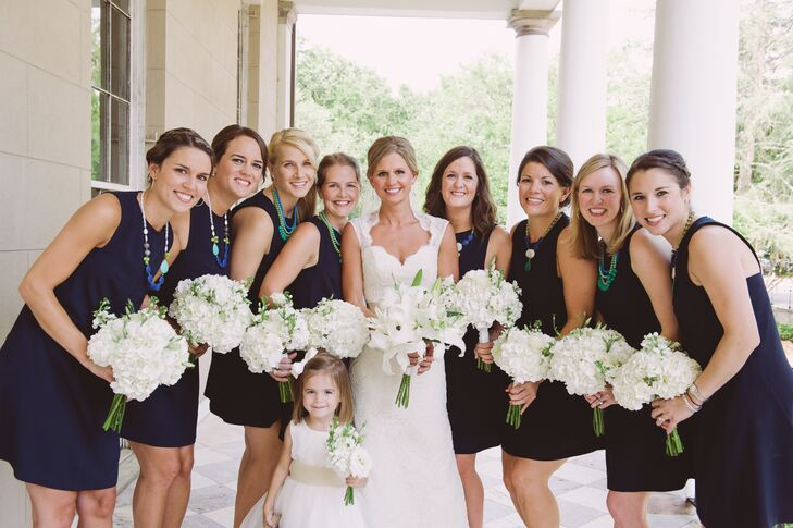 The bridesmaids wore classic, simple navy J.Crew dresses to match the chic wedding look. They completed their attire with blue and green statement necklaces for a little added glamour.