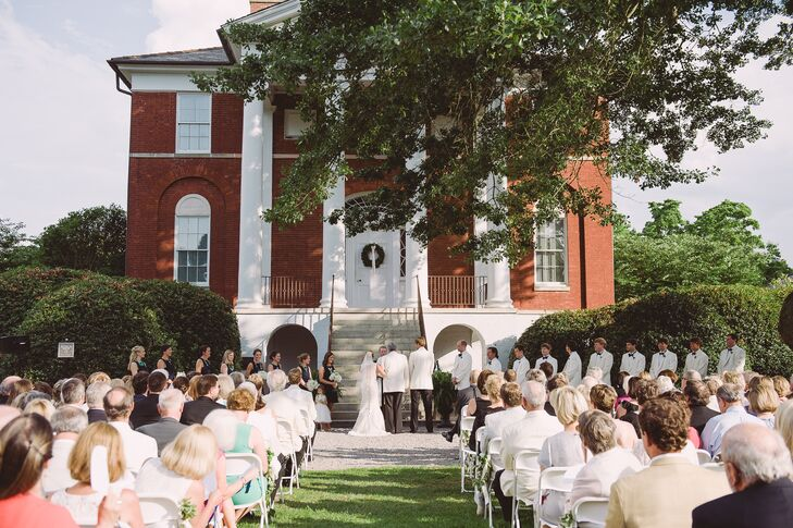 """Claire and Adam exchanged vows on the front lawn of the Robert Mills House in Columbia, South Carolina. """"It ended up being even warmer than a typical June day, but the large silent fans, lemonade and water stands and the programs shaped like fans helped guests stay cool during the joyful 15-minute ceremony,"""" Claire says. They loved the historic charm of the venue with the gorgeous brick and white pillars."""