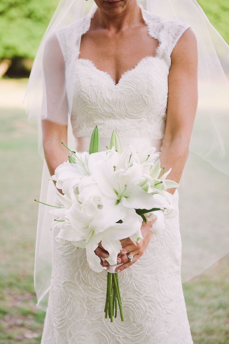 Claire carried lush white lilies in her bouquet for a simple, classic look. The stems were wrapped in white satin ribbon with the long stems exposed. The bridesmaids carried white hydrangeas to match the all white-color palette.
