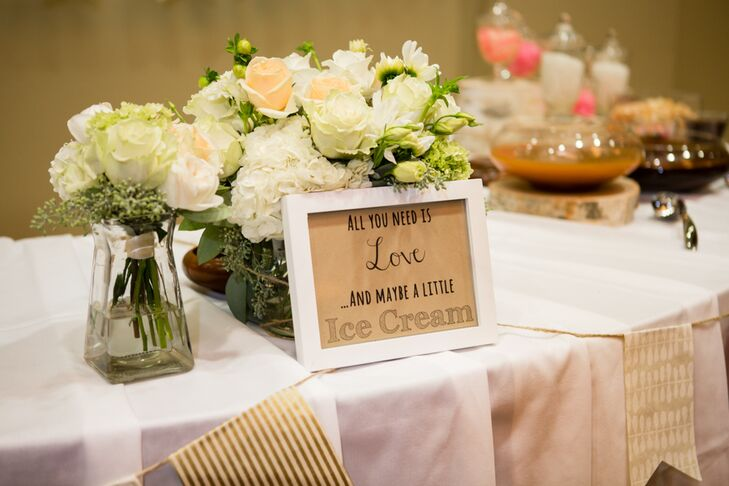 """At the reception, a sign that read """"All you need is love and maybe a little ice cream"""" marked the ice cream bar location. In addition to the savory treat, guests also enjoyed the two-tiered wedding cake designed to look like a birch tree."""