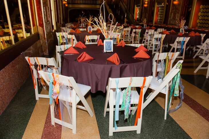 Bright decorations covered the tables and chairs. The tables held the earthy palette of brown and moss while the chairs brought in a pop of colour. Each was wrapped in different coloured and patterned ribbons.