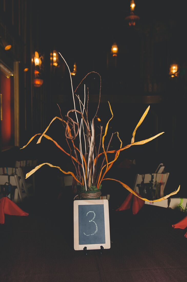 The centerpieces were made of branches, moss and some fun orange pieces the bride and groom found at a craft store. They crafted all of the centrepieces themselves!