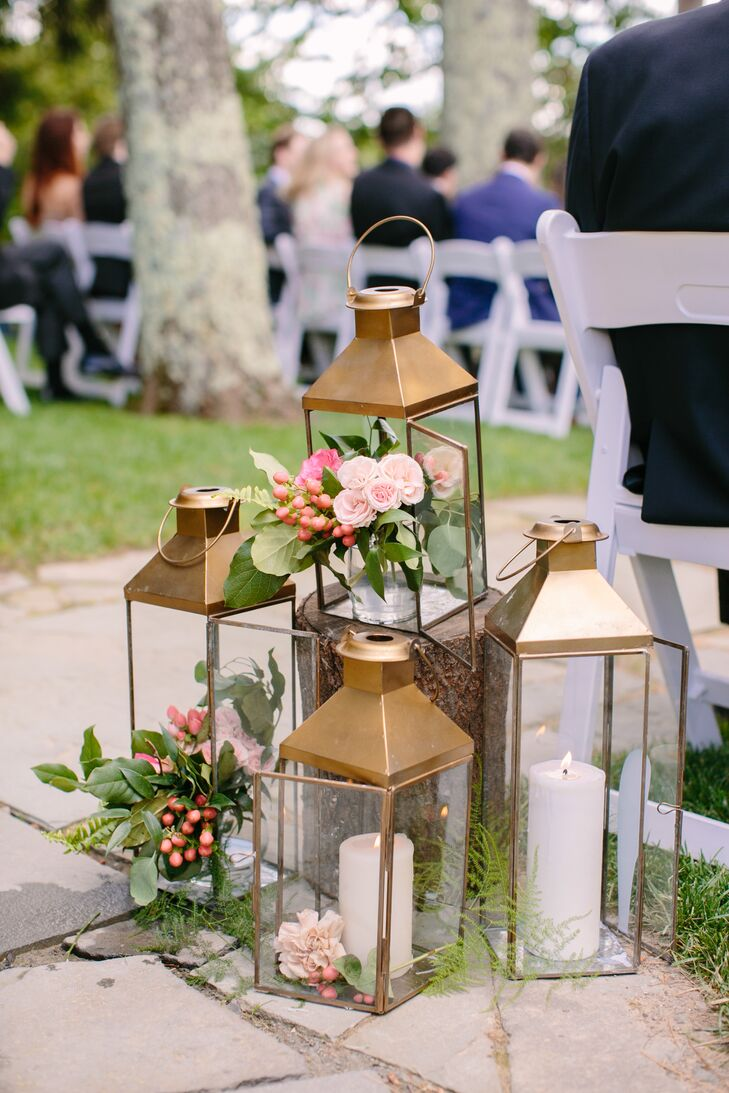 Though the ceremony took place in the afternoon, clusters of gold lanterns filled with flickering pillar candles and fresh blooms gave the dramatic outdoor setting a sense of romance and intimacy.