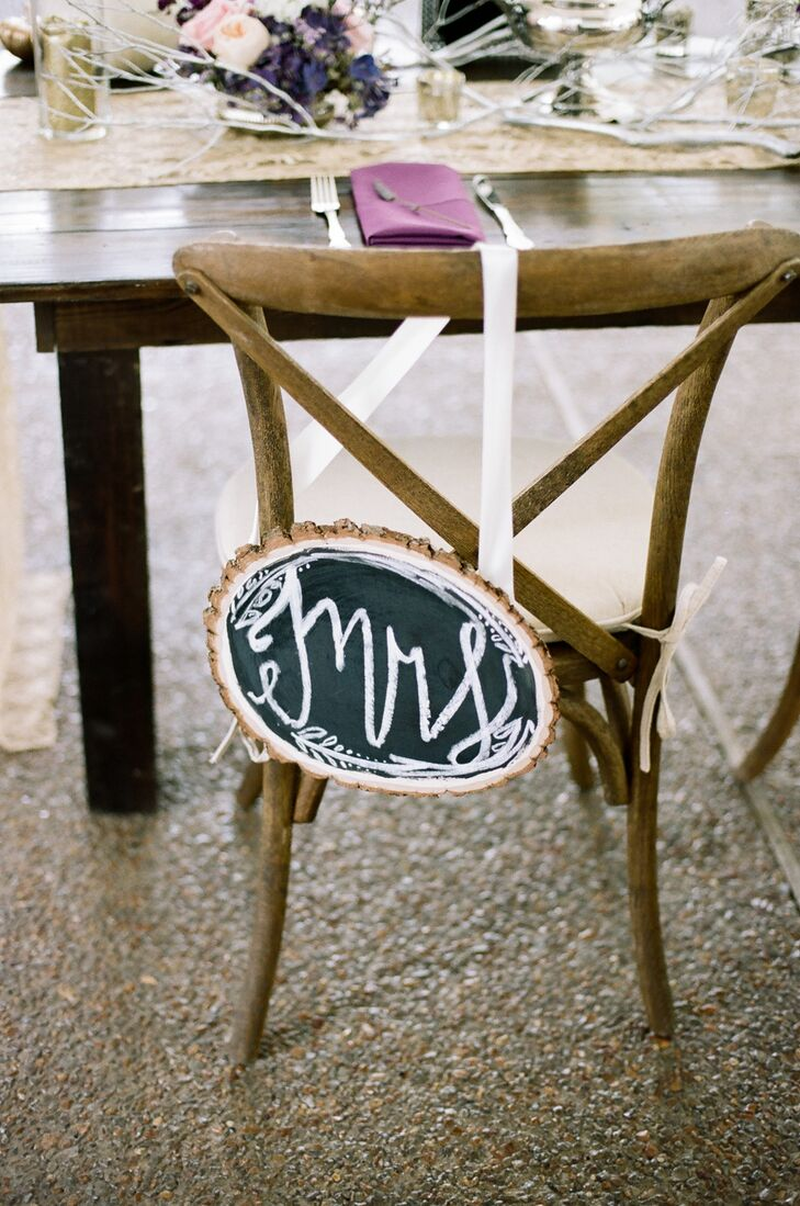 To play up the wedding's subtle rustic undertones, the couple incorporated details like handcrafted chalkboard chair signs, wooden farm tables, pumpkins and silvery branches throughout the reception decor.
