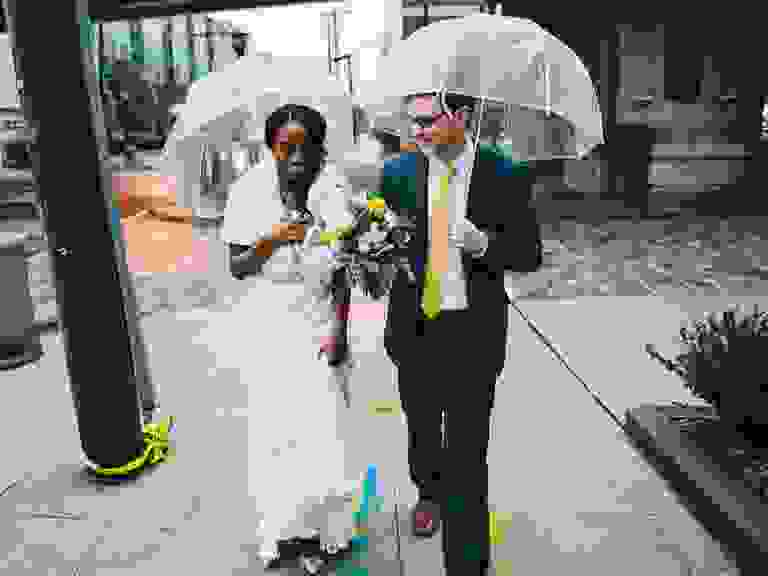Bride and groom walking in Brooklyn, New York with clear umbrellas