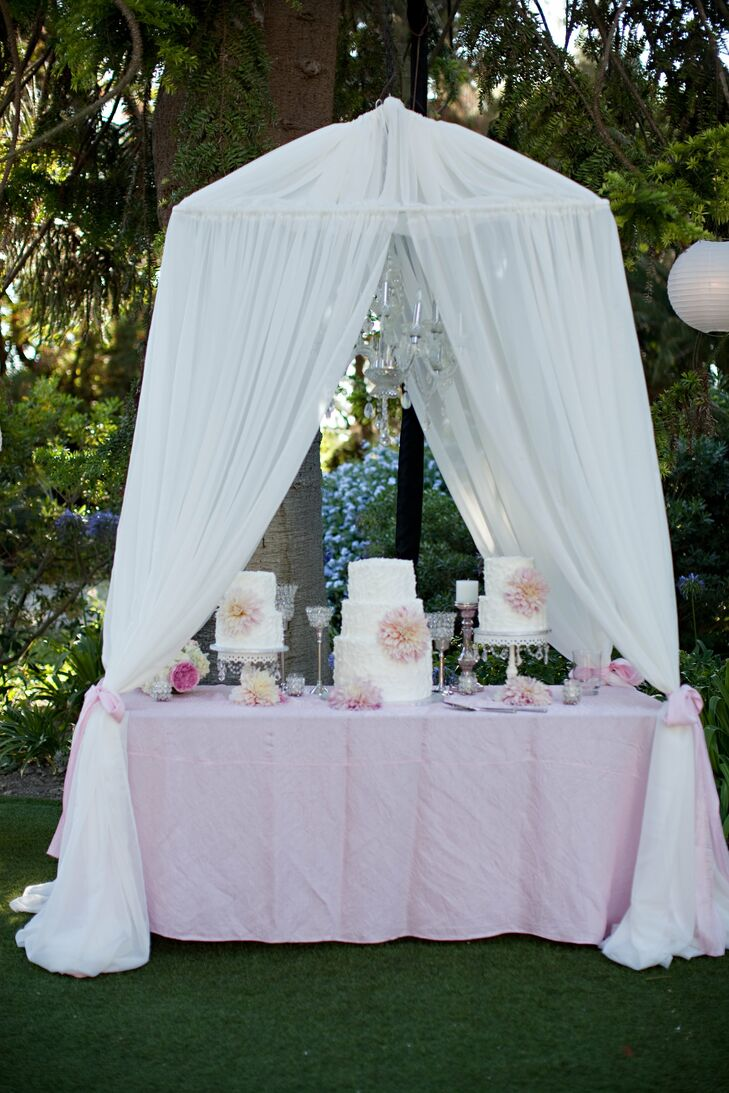 The three wedding cakes were displayed on a table beneath a glittery chandelier and surrounded by gauzy white fabric.