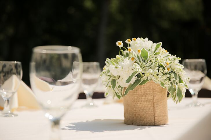 The couple chose rustic centerpieces of floral arrangements set in low vases that were wrapped in burlap.