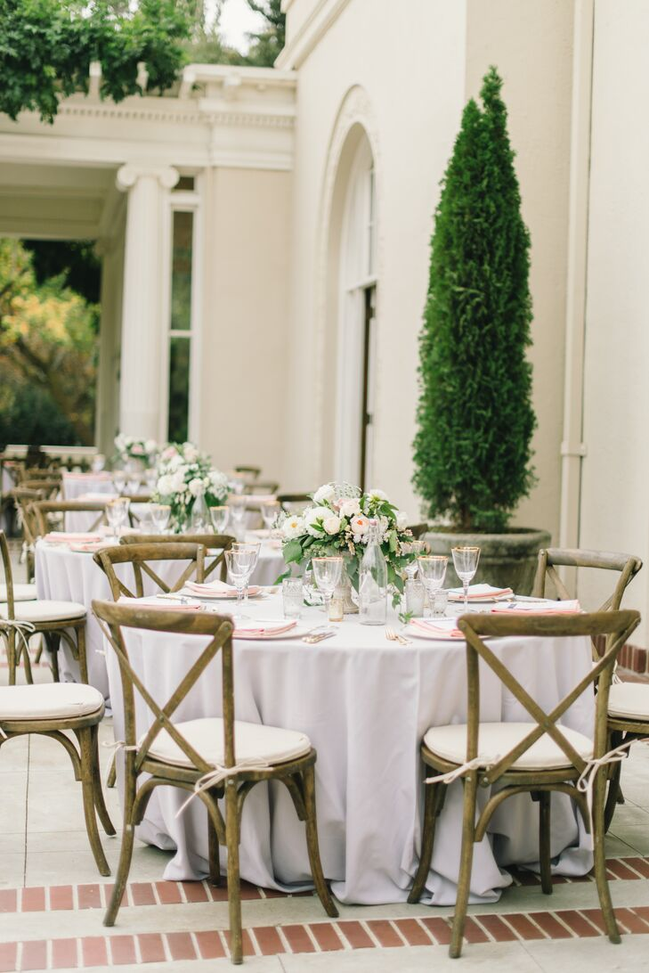 Light gray linen-covered tables were set with gold-­accented ivory china, elegant gold flatware and gold­-rimmed glassware. Atop each place setting sat a peach napkin and a dinner menu with dusty blue font. Vintage glass water bottles with white script numbers served as table identifiers.