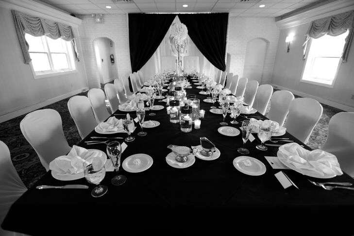 The long head table at the wedding reception was dressed in a lack tablecloth and had white dinnerware set.