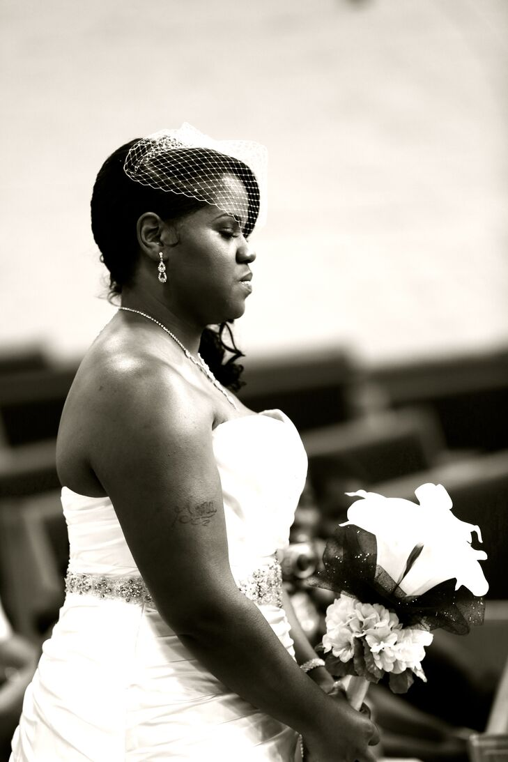 Gena walked down the aisle wearing her ivory strapless wedding dress accented with a crystal belt.