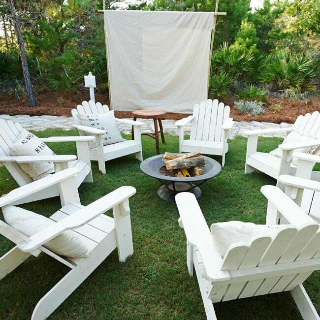 White adirondack chairs sat around a fire pit for late-night s'mores.
