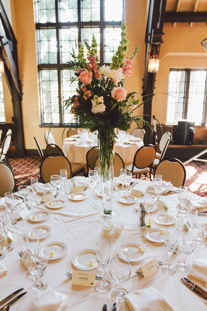 The round tables were decorated with high centerpieces in clear glass vases. The arrangements were composed of snapdragons, roses, stock and Peruvian lilies in white and shades of pink.
