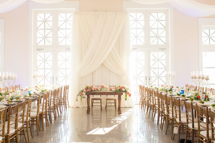 The interior of Namar Event Center in South Padre Island, Texas, was just as impressive as the outside: It had elegant ivory drapery and oversize windows that let in lots of natural light. Rustic family-style dining tables and chiavari chairs enhanced the elegant beachy atmosphere.
