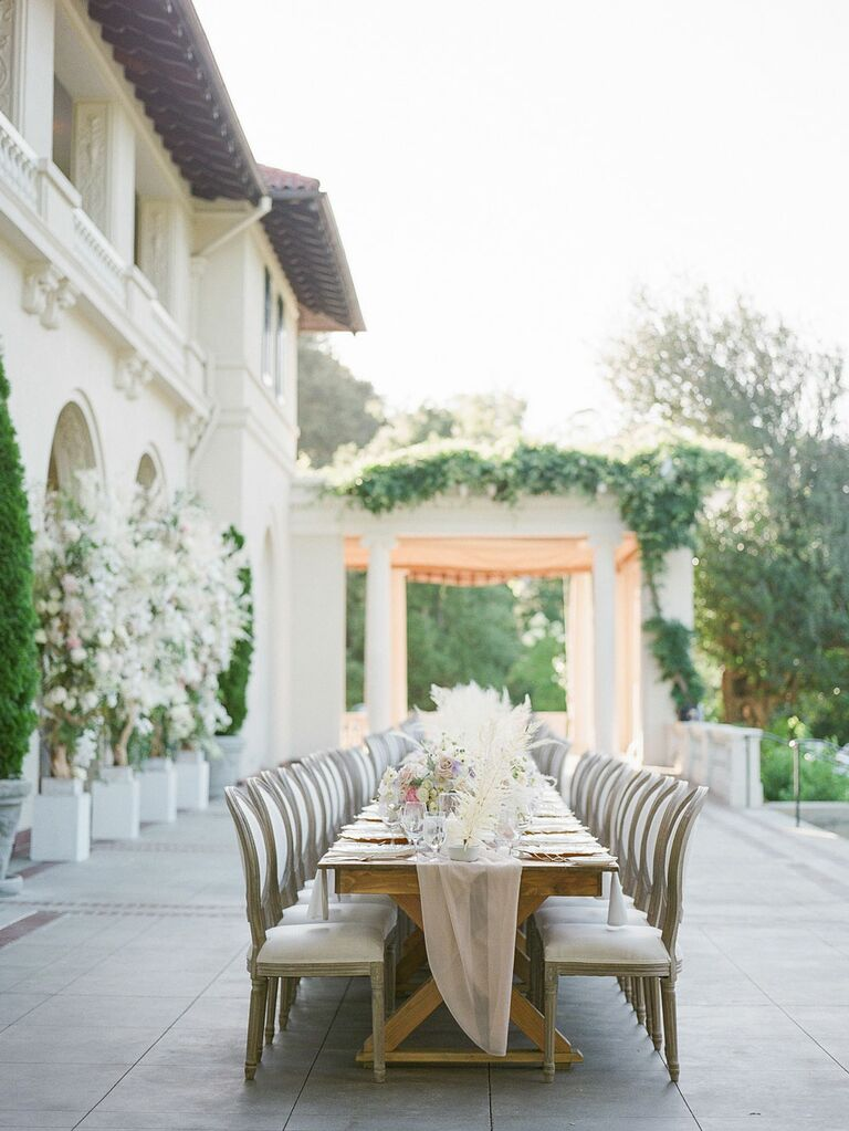 Romantic outdoor wedding venue with long table and gauzy runner