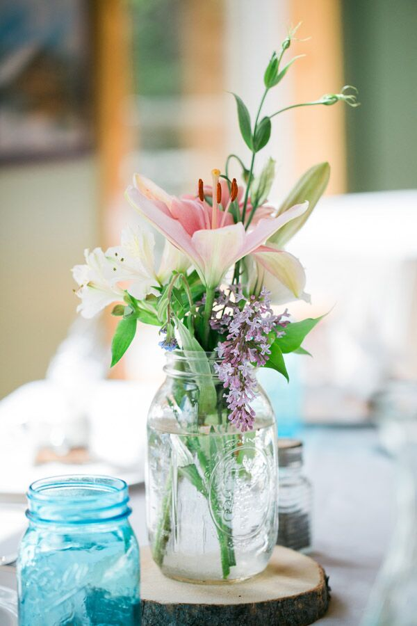 Centerpieces at the reception were made up of mason jars on tree rings. The mason jars were filled with lilies, alstroemerias and hyacinths.