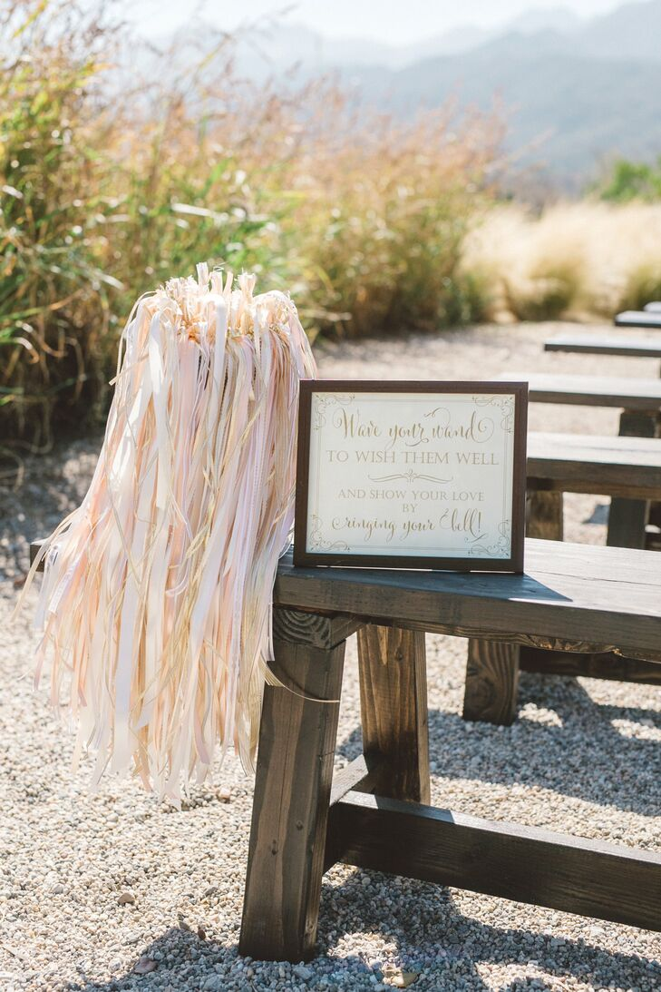 As guests took their seats, they were encouraged to take a pale pink ribbon wands and wave them as the newlyweds walked up the aisle.