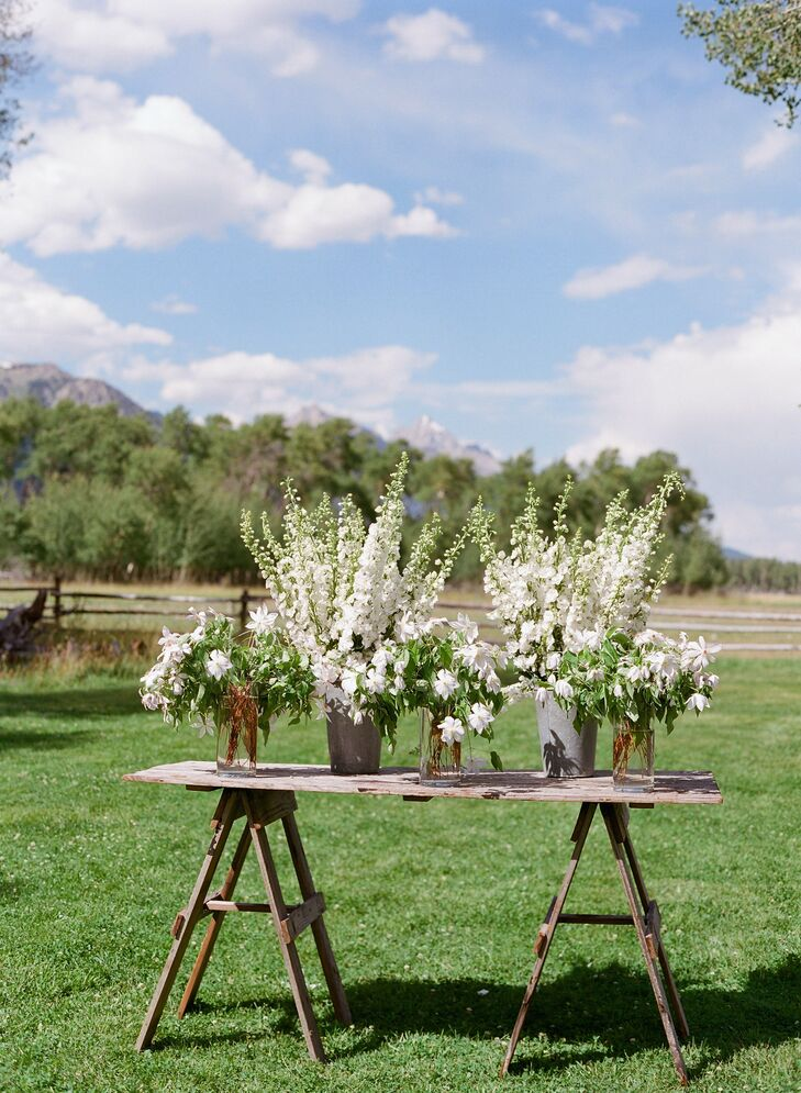 The couple created an altar out of a rustic wooden table, which they topped with vases of white delphiniums and clematis.