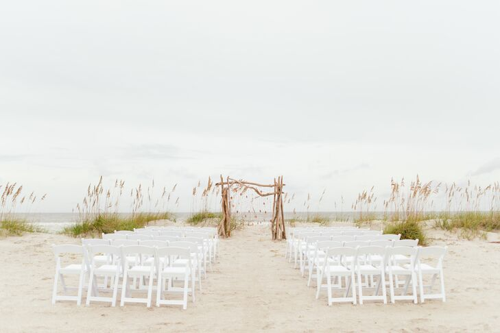 Taking advantage of their venue's waterfront locale, Noelle and Patrick gathered together their friends and families on the beach, where they exchanged vows with their toes in the sand. The pair let the scenery speak for itself by keeping the decor simple, adding but a driftwood wedding arch to the end of the aisle.