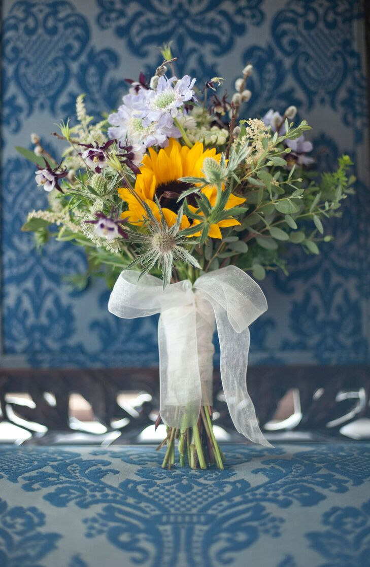 """Heather carried a bouquet with thistles, sunflowers and other wildflowers on her wedding day. """"I found Gabriele from Gabriele's Hand Designs, a florist who specializes in very natural-looking bouquets,"""" Heather says."""