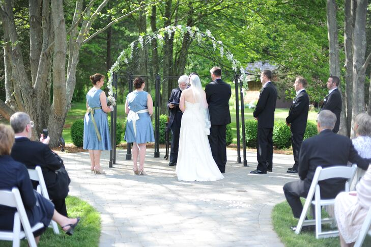 Heather and Chris were married under a wedding arch decorated with greens and blue flowers at their outdoor ceremony in Branford, Connecticut.