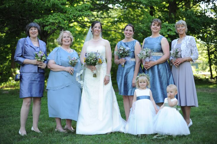 """Heather wore a strapless, A-line wedding dress by Sareh Nouri in the style of """"Isadora."""" She paired it with a lace-trim fingertip veil. Her bridesmaids wore knee-length sea blue dresses, and her female relatives matched them in similarly colored dresses."""