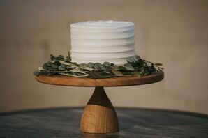 Single-Tiered Wedding Cake with Wooden Stand and Greenery