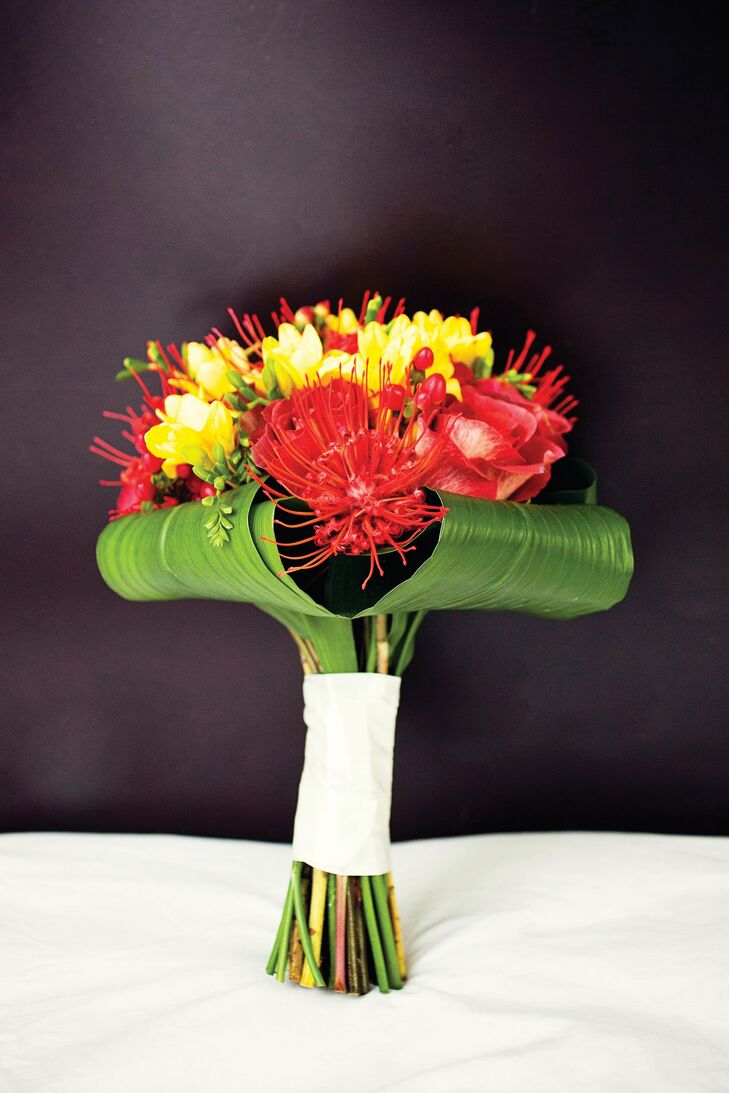 The bride carried red pincushion proteas, roses and yellow freesias in her nontraditional bouquet.
