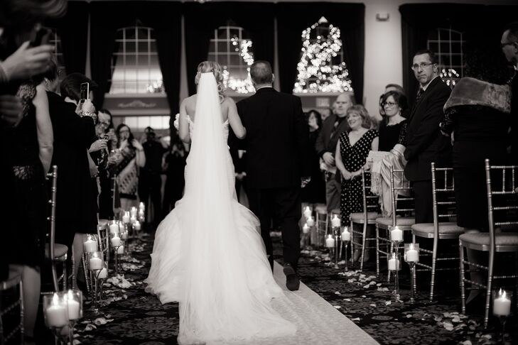 The ballroom ceremony had an aisle lined with floating candles and petals. Megan wore a chapel-length veil to her ceremony.