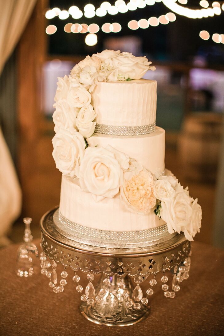 Nikki and Scott enjoyed a three-tier white wedding cake with raspberry filling. Silver rhinestones wrapped around the base of each layer, and the cake was topped with cascading white roses.