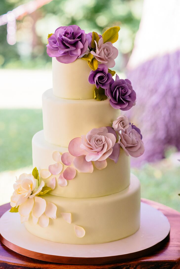 A cascade of fondant purple ombre flowers decorated the white cake.
