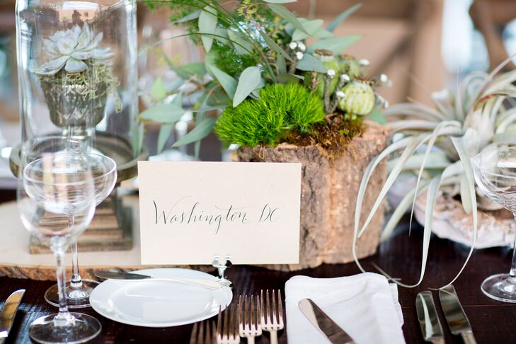 Ivory paper table names with whimsical calligraphy labeled each table with the name of one of Faith and Brent's favorite cities.