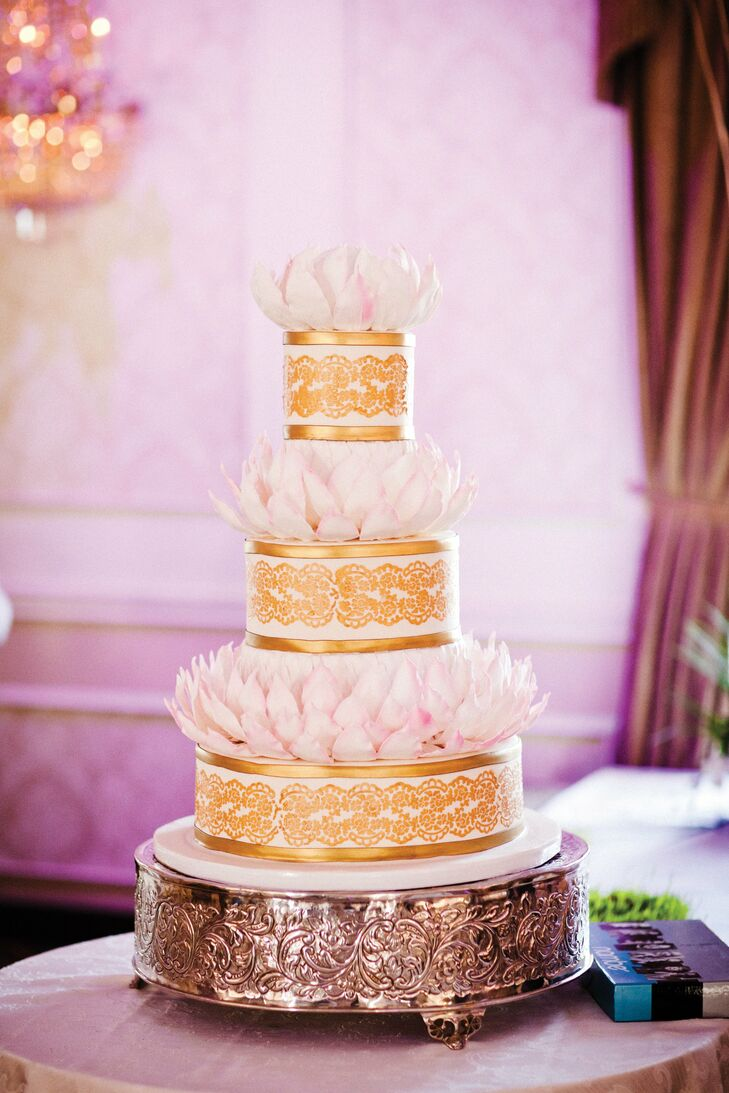 The elaborate gold-and-blush cake played up the couple's wedding logo—a lotus flower—with leaves made out of gum paste.