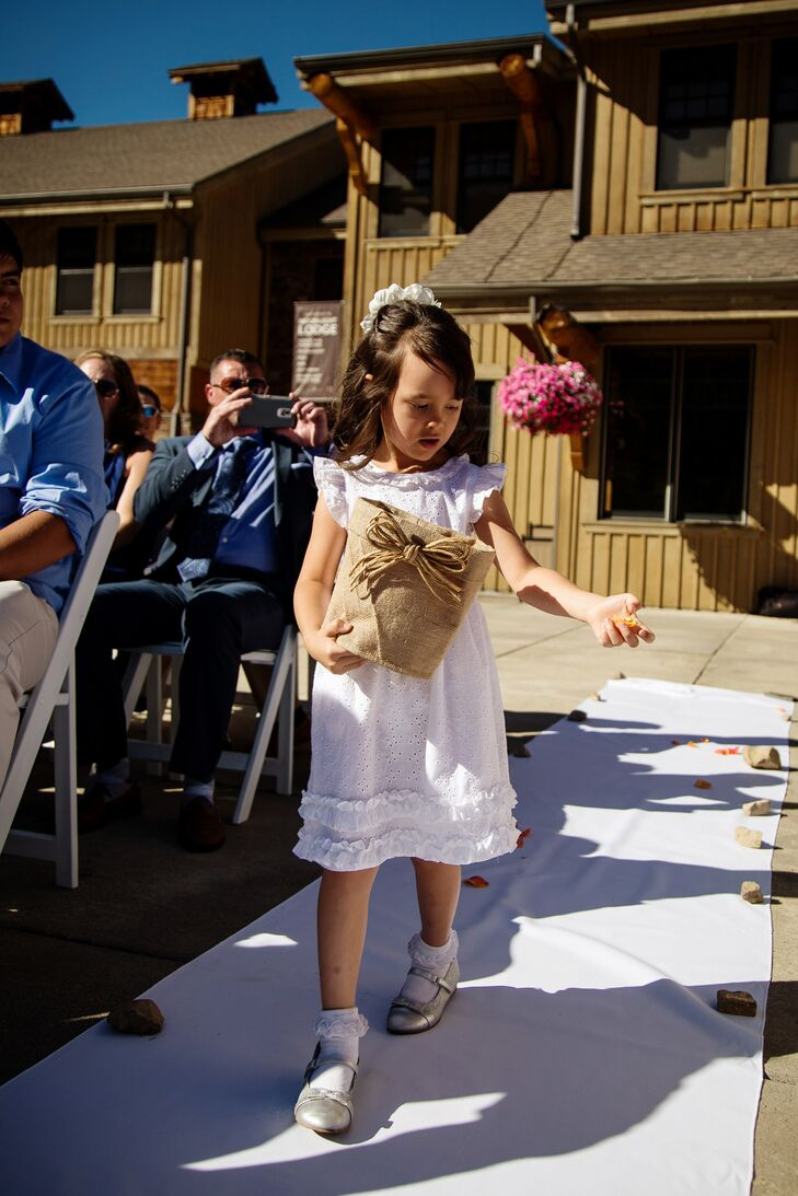 The flower girl carried colorful rose petals in a burlap basket decorated with a raffia bow down the aisle. The rustic bucket went with the wedding's mountaintop vibe.