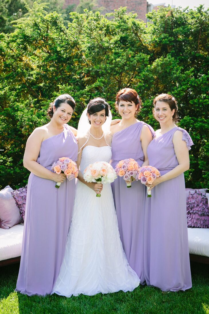Carey's bridesmaids all wore floor-length, one-shoulder dresses in a lavender chiffon fabric. They carried bouquets of lavender and coral roses.