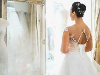 bride trying on wedding dress at bridal salon