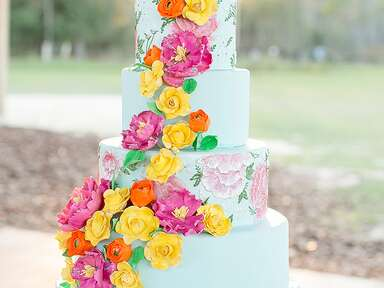 Bright blue wedding cake with bright sugar flowers and handpainted designs