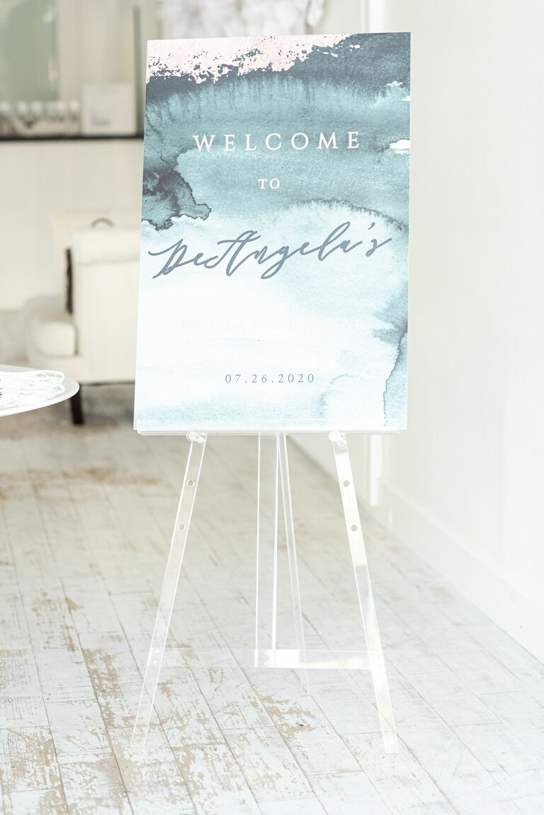 Blue watercolor welcome sign on acrylic easel