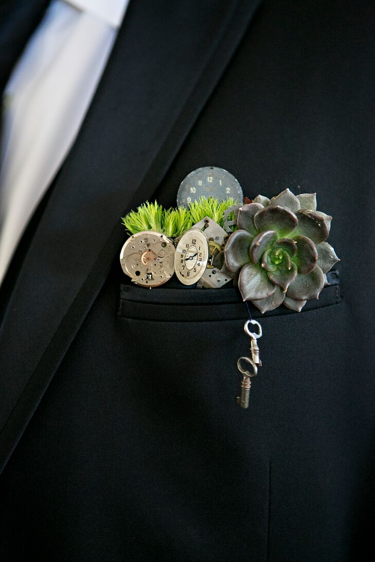 "As a celebration of their first Christmas together, David gave Lee a watch-detailed money clip engraved with ""time stood still when I met you."" For their wedding, David and Lee wore this industrial pocket square covered with parts from a deconstructed clock to acknowledge the saying. A succulent and green dianthus also tied in their rustic vibe."